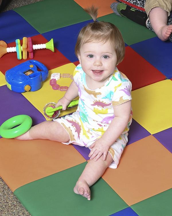 Baby girl sitting on colorful rug