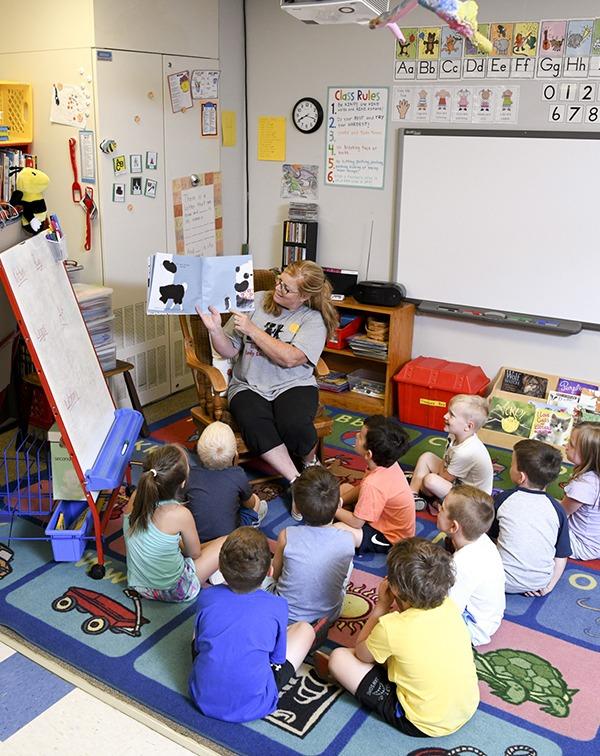 preschool kids gathered around as teacher reads outloud
