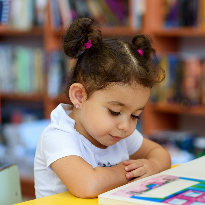Little girl sitting at table reading a book