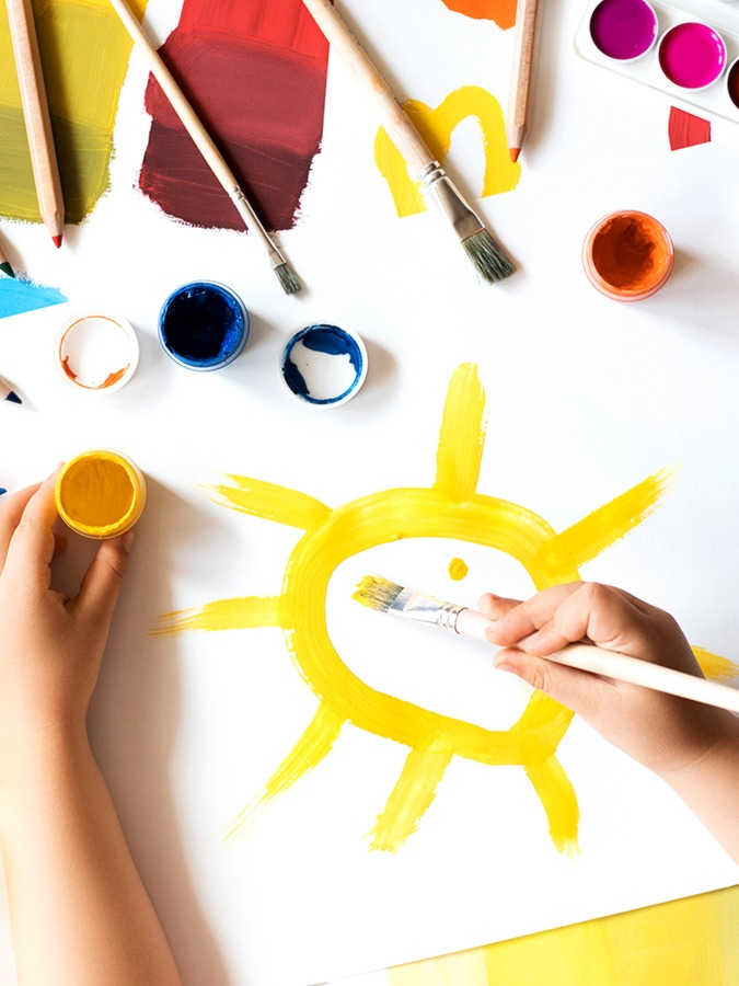 Child painting yellow sun on white paper